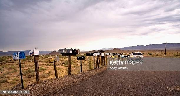 USA, Arizona, Car by row of mailboxes on country road leading to trailer park
