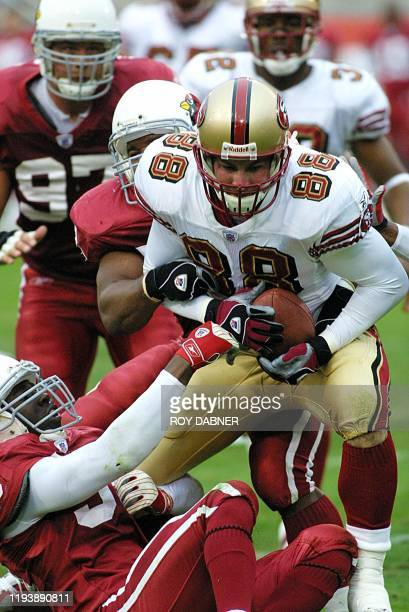 Arizona Cardinals David Barrett and Kwamie Lassiter tackle San Francisco 49ers Justin Swift after a pass reception from Cardinals Jeff Garcia during...