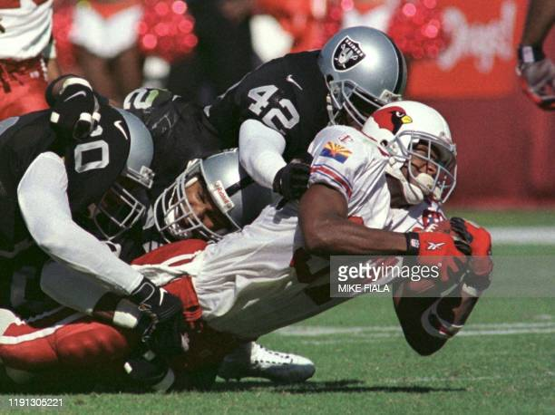 Arizona Cardinals fullback Larry Centers is brought down by Oakland Raiders safety Eric Turner and Richard Harvey during first half action at Sun...