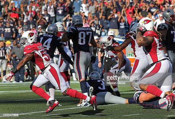 Arizona Cardinals outside linebacker O'Brien Schofield celebrates over a distraught New England Patriots kicker Stephen Gostkowski , laying face down...