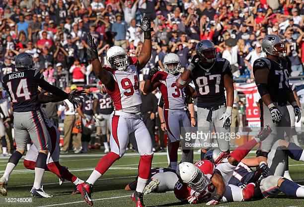 Arizona Cardinals outside linebacker Sam Acho celebrates over a prostrate New England Patriots kicker Stephen Gostkowski who missed a potential game...