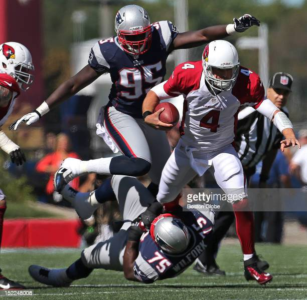 Arizona Cardinals quarterback Kevin Kolb is chased down by New England Patriots defensive tackle Vince Wilfork and New England Patriots defensive end...