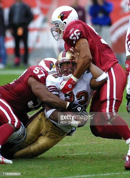 Arizona Cardinals Ronald McKinnon and LeVar Woods tackle San Francisco 49ers runningback Kevan Barlow after a pass reception from 49ers Jeff Garcia...