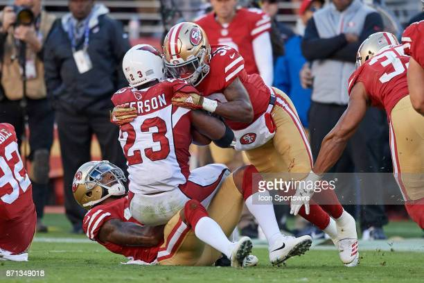 Arizona Cardinals running back Adrian Peterson is tackled by San Francisco 49ers defensive back Adrian Colbert and San Francisco 49ers cornerback...