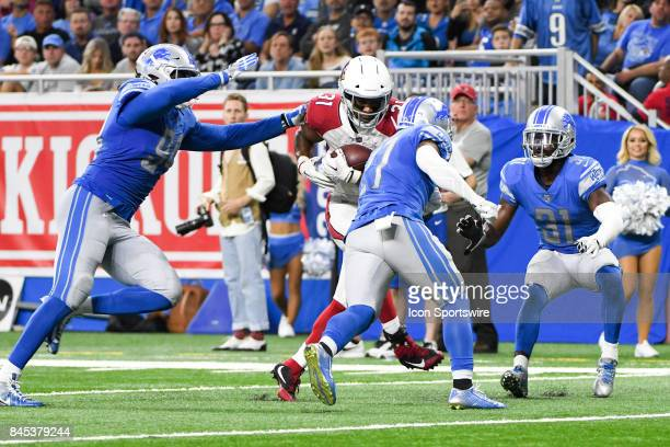 Arizona Cardinals running back David Johnson catches the ball and is tackled by Detroit Lions defensive end Jeremiah Ledbetter and Detroit Lions free...