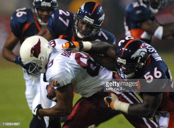 Arizona Cardinals wide receiver David Boston is tackled by Denver Broncos cornerback Denard Walker and linebacker Al Wilson during the third quarter...