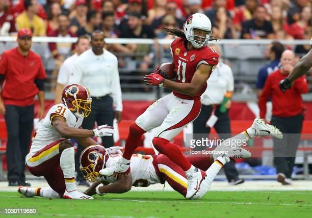 Arizona Cardinals wide receiver Larry Fitzgerald makes a catch as Washington Redskins cornerback Fabian Moreau and Washington Redskins defensive back...