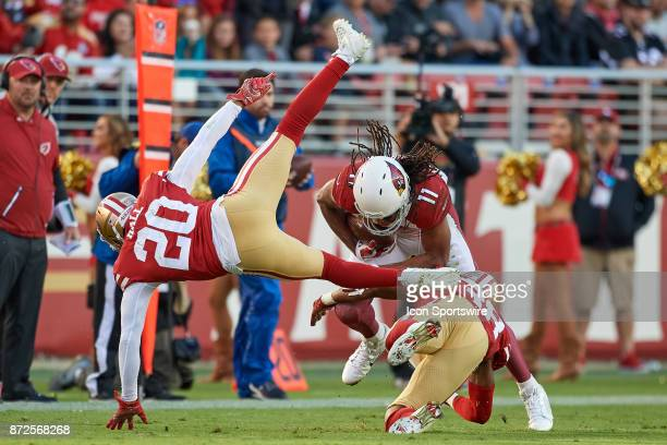 Arizona Cardinals wide receiver Larry Fitzgerald runs with the football as he battles with San Francisco 49ers defensive back Adrian Colbert and San...