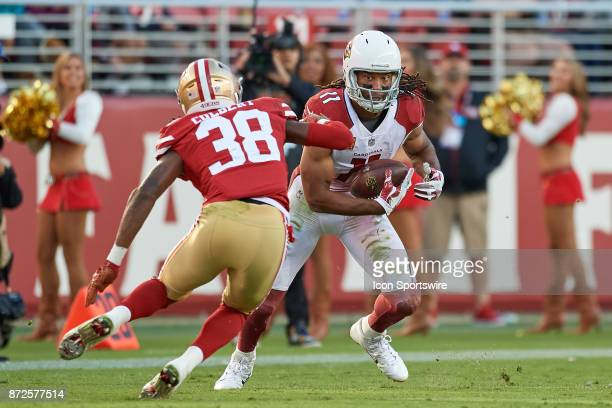 Arizona Cardinals wide receiver Larry Fitzgerald runs with the football as he battles with San Francisco 49ers defensive back Adrian Colbert during...