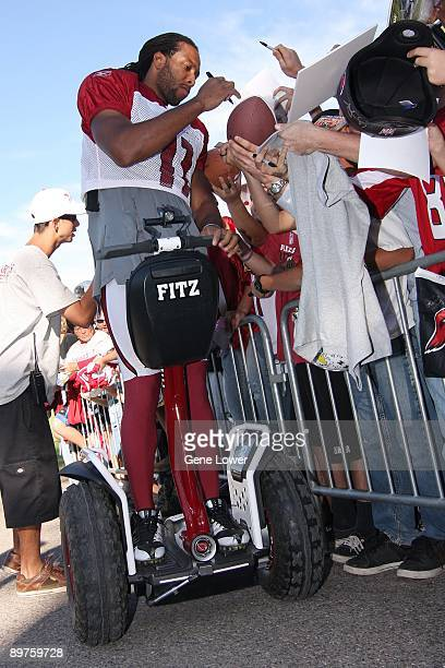 Arizona Cardinals wide receiver Larry Fitzgerald stops while on his segway to sign autographs for the fans during training camp on August 7 2009 in...
