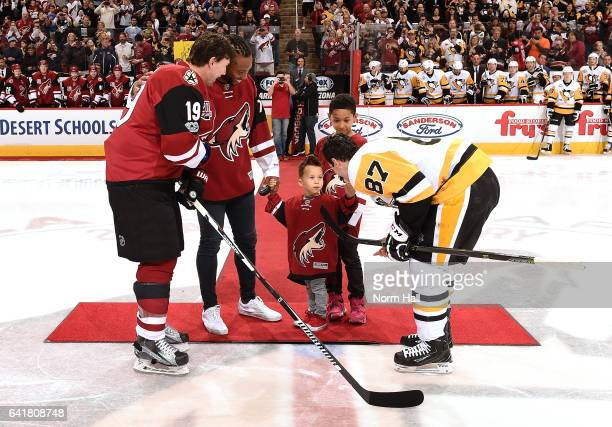 Arizona Cardinals wide receiver Larry Fitzgerald with his sons Apollo and Devin prepare to drop the puck between Shane Doan of the Arizona Coyotes...