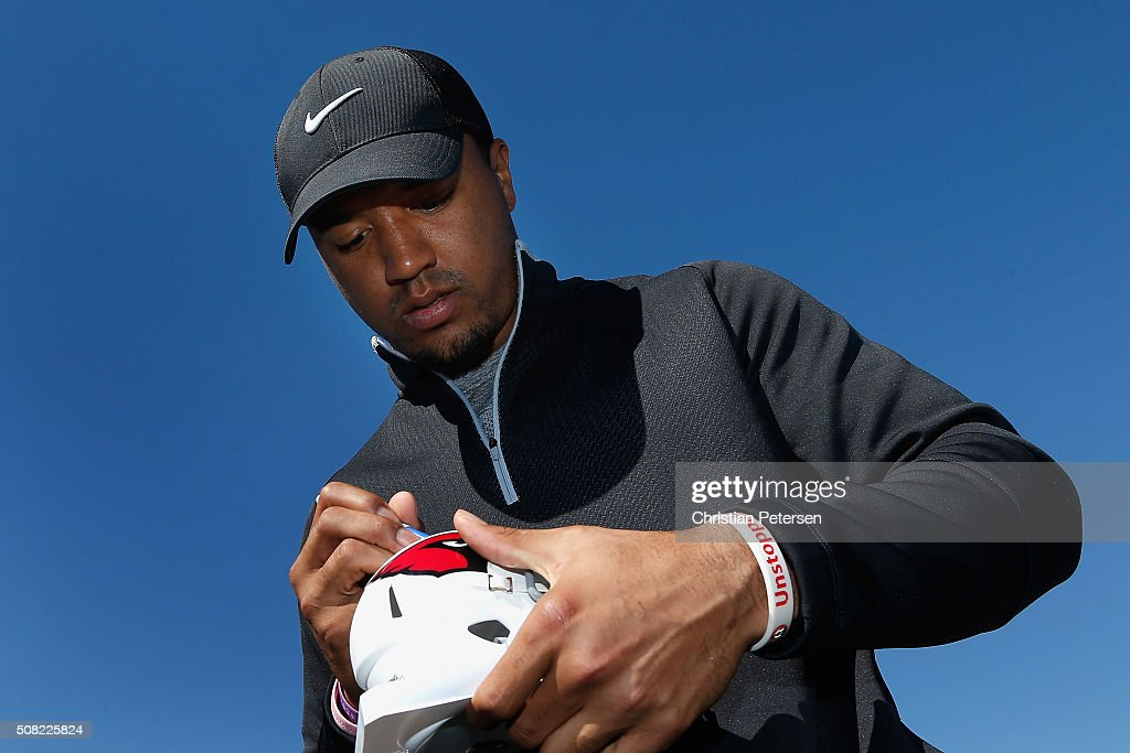Arizona Cardinals wide receiver Michael Floyd signs an autograph for fans on the 18th green following the pro-am for the the Waste Management Phoenix Open at TPC Scottsdale on February 3, 2016 in Scottsdale, Arizona.