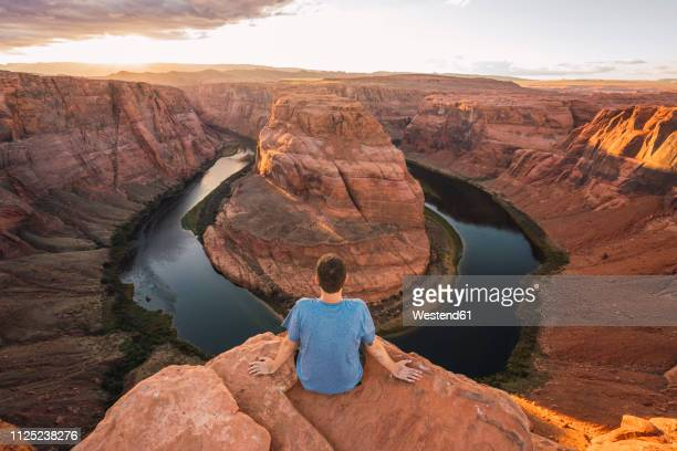 usa, arizona, colorado river, horseshoe bend, young man sitting on viewpoint - national park stock pictures, royalty-free photos & images
