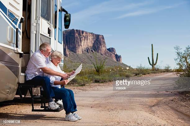 USA, Arizona, Couple on desert road looking at map