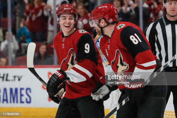 Arizona Coyotes center Clayton Keller smiles while celebrating with Arizona Coyotes center Phil Kessel during the NHL hockey game between the...