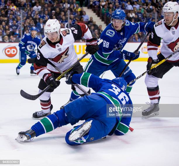 Arizona Coyotes Center Josh Archibald and Defenceman Jakob Chychrun battle with Vancouver Canucks Left Wing Jussi Jokinen and Center Adam Gaudette...