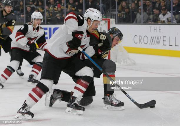 Arizona Coyotes center Nick Cousins and Vegas Golden Knights defenseman Nate Schmidt battle for control of the puck during a regular season game...