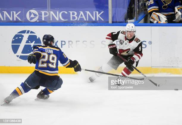 Arizona Coyotes forward Clayton Keller and St. Louis Blues defenseman Vince Dunn go after a loose puck during an NHL game between the Arizona Coyotes...