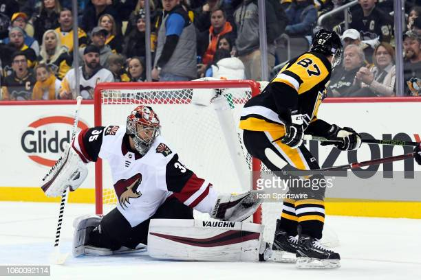 Arizona Coyotes Goalie Darcy Kuemper makes a save on Pittsburgh Penguins Center Sidney Crosby during the first period in the NHL game between the...