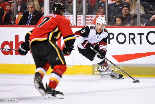 Arizona Coyotes Left Wing Taylor Hall skates with the puck toward Calgary Flames Defenceman TJ Brodie during the second period of an NHL game where...