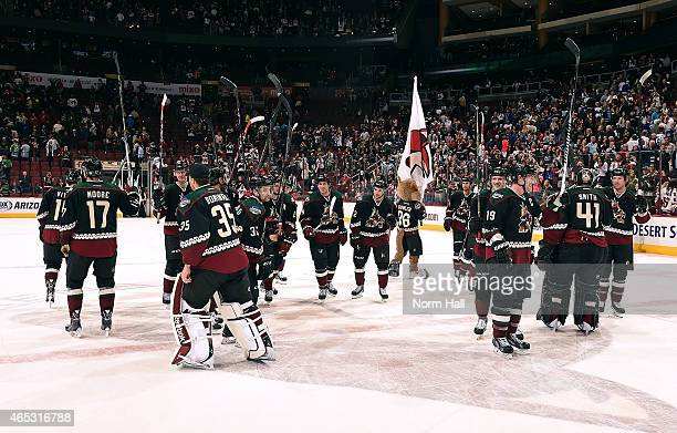 Arizona Coyotes players salute the fans on Throwback Night following a 32 overtime shootout victory against the Vancouver Canucks at Gila River Arena...