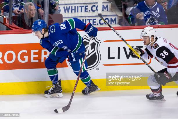 Arizona Coyotes Right Wing Christian Fischer battles with Vancouver Canucks Center Adam Gaudette during the third period in a NHL hockey game on...