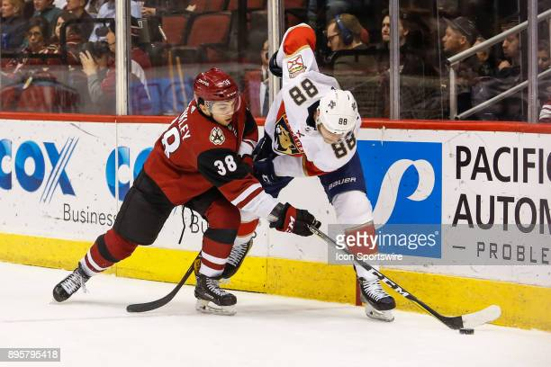 Arizona Coyotes right wing Nicholas Merkley fights for the puck with Florida Panthers left wing Jamie McGinn during the NHL hockey game between the...