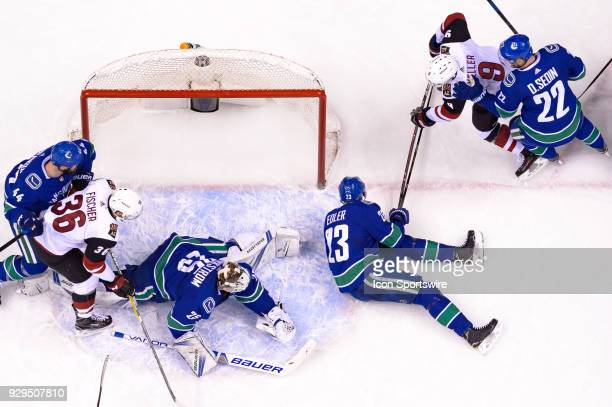 Arizona Coyotes Winger Clayton Keller digs for the puck under Defenceman Alexander Edler and scores a goal on Vancouver Canucks Goalie Jacob...