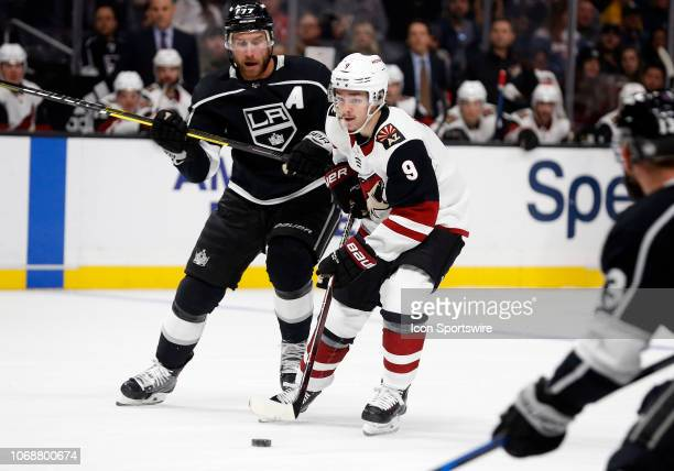 Arizona Coyotes winger Clayton Keller dribbles between Los Angeles Kings center Jeff Carter and Los Angeles Kings left wing Kyle Clifford during the...
