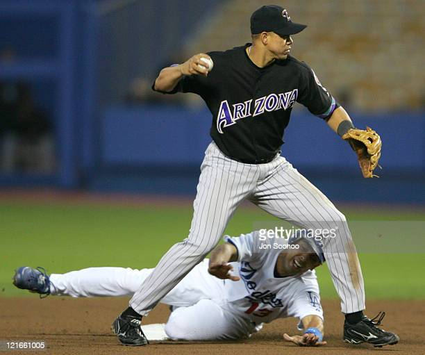 Arizona Diamondbacks Alex Cintron turns a double play aftergetting Alex Cora of the Los Angeles Dodgers out at second base during the 14 loss to the...