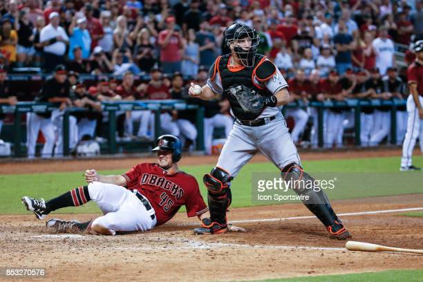 Arizona Diamondbacks left fielder Kris Negron slides home after being out on the force by Miami Marlins catcher JT Realmuto during the MLB baseball...