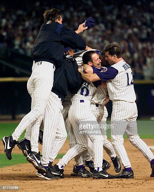 Arizona Diamondbacks left fielder Luis Gonzalez is mobbed by teammates Randy Johnson and Steve Finley after Gonzalez hit an RBI single in the bottom...