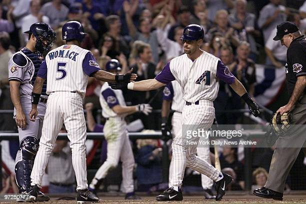 Arizona Diamondbacks' Luis Gonzalez is congratulated by teammate Tony Womack after hitting a tworun homer in the third inning of Game 1 of the World...