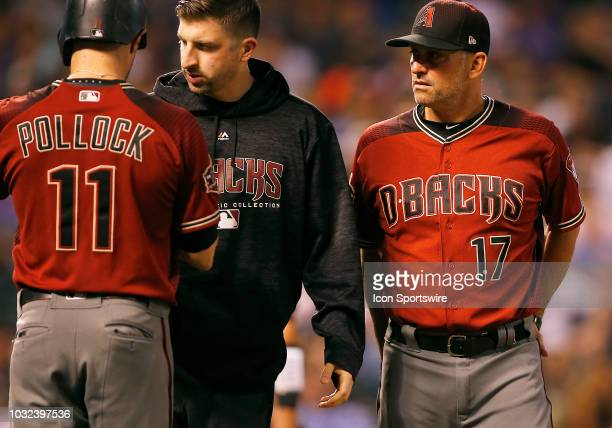 Arizona Diamondbacks manager Torey Lovullo and trainer check on outfielder AJ Pollock following a hit by pitch during a regular season game between...