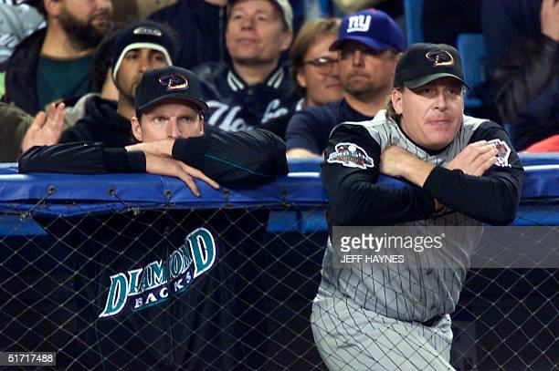 Arizona Diamondbacks pitchers Curt Schilling and Randy Johnson watch the play from the dugout during thef fifth inning of Game 5 of the World Series...
