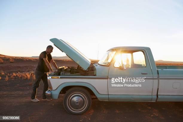 USA, Arizona, Man repairing broken pick-up truck