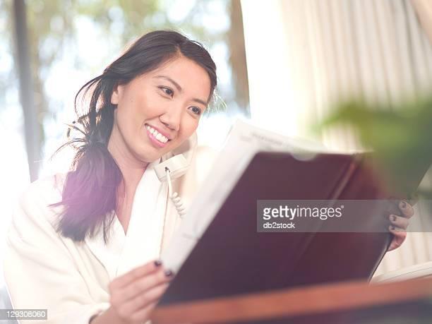 USA, Arizona, Scottsdale, Woman ordering room service in hotel
