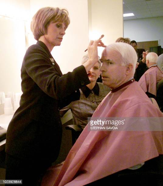 US Arizona Senator and Republican presidential hopeful John McCain sits while a Local TV station makeup person helps him with makeup before...