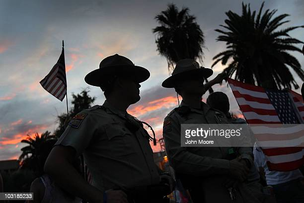 Arizona state policemen stand between supporters and opponents of Arizona's immigration enforcement law during a demonstration against illegal...