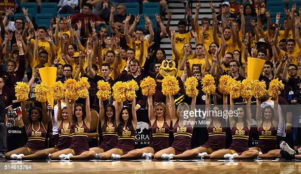 Arizona State Sun Devils cheerleaders and fans hold their arms up during a firstround game of the Pac12 Basketball Tournament against the Oregon...