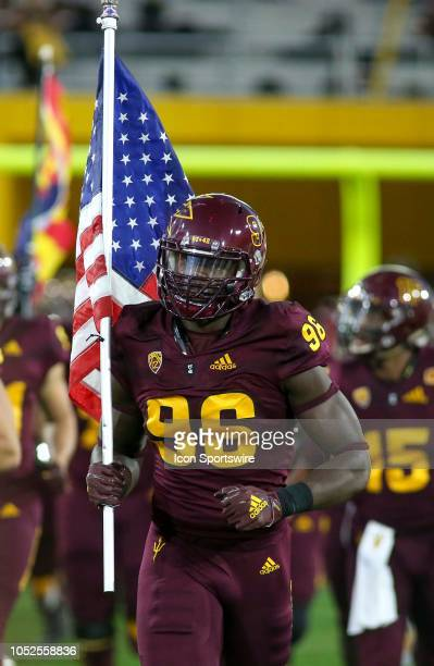 Arizona State Sun Devils defensive lineman Jalen Bates runs onto the field with the US Flag before a college football game between the Arizona State...