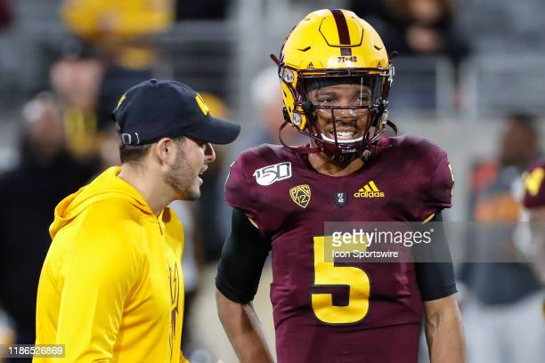 Arizona State Sun Devils quarterback Jayden Daniels smiles while talking to a coach before the college football game between the Arizona Wildcats and...