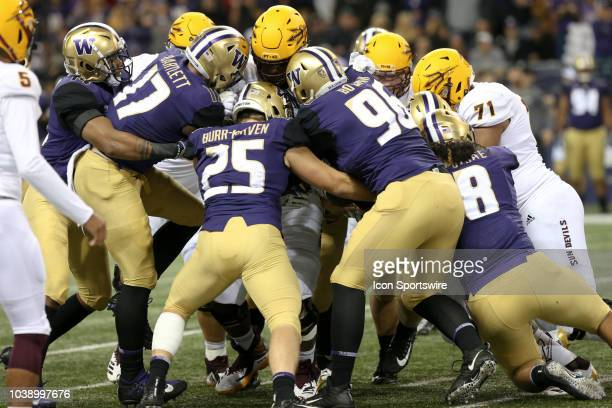 Arizona State's Eno Benjamin gets wrapped up by a swarm of Washington players during the college football game between the Washington Huskies and the...