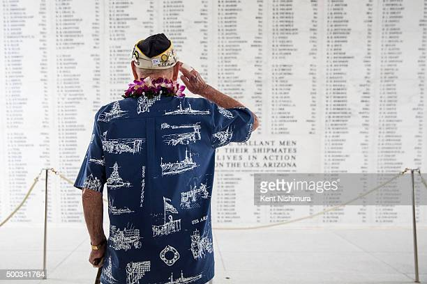 S Arizona survivor Lou Conter salutes the Arizona Remembrance Wall during a memorial service marking the 74th Anniversary of the attack on the US...