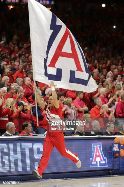 Arizona Wildcats cheerleader runs onto the court with a flag during the a college basketball game between Arizona State Sun Devils and the Arizona...