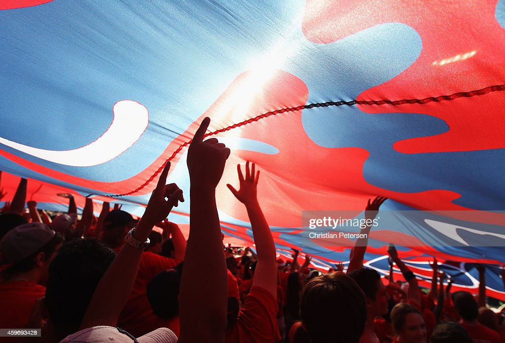 Arizona Wildcats fans hold up a large flag in celebration during the Territorial Cup college football game against the Arizona State Sun Devils at Arizona Stadium on November 28, 2014 in Tucson, Arizona. The Wildcats defeated the Sun Devils 42-35 to win the PAC-12 south championship.