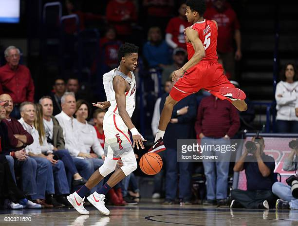 Arizona Wildcats guard Kobi Simmons dribbles around New Mexico Lobos guard Jalen Harris during the first half of the college basketball game at...