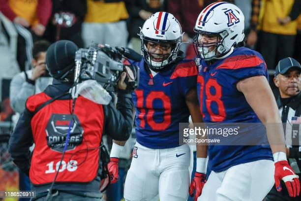 Arizona Wildcats wide receiver Jamarye Joiner and Arizona Wildcats offensive lineman Donovan Laie celebrate after a touchdown in front of a TV camera...