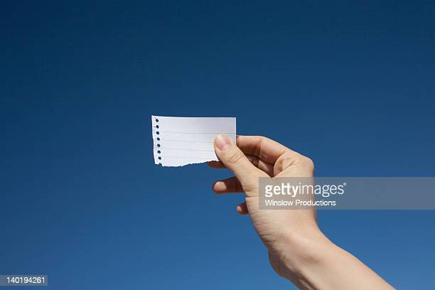 USA, Arizona, Winslow, Hand of woman holding paper note against blue sky