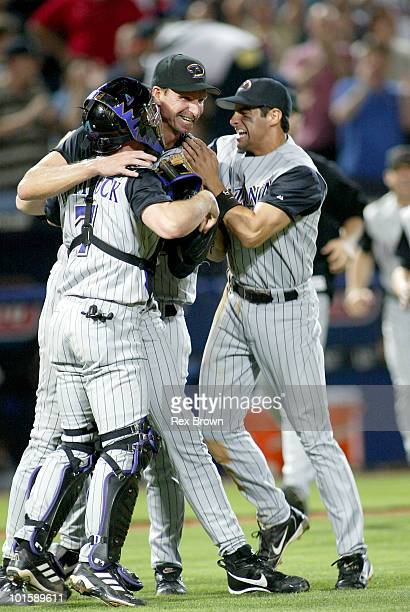 Arizona's Randy Johnson gets congratulations from teammates Robby Hammick and Alex Cintron after pitching a perfect game against the Braves May 18 at...